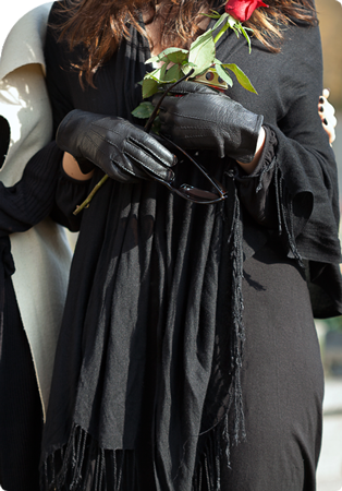 woman holding a rose while attending a funeral